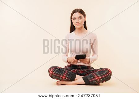 Pretty young brunette girl dressed in pajamas holding ebook while sitting with legs crossed isolated over pink background