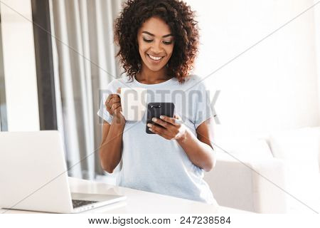 Smiling african woman using mobile phone while holding cup of coffee and sitting with laptop computer at home