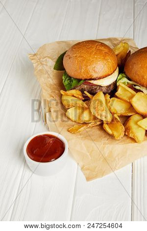 Tempting fast food diner with hamburgers and potato fries served on white table poster