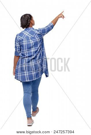 Back view of a young black girl in jeans and a checkered shirt. going girl showing.  backside view of person.   Isolated over white background. A girl in a shirt saw something on a walk
