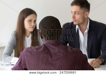 Back View Of African American Consultant Talking To Doubtful Millennial Couple, Workers Feeling Unsu