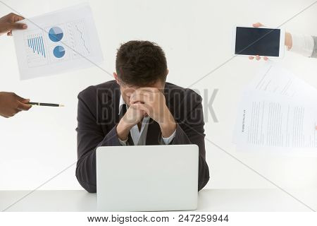 Depressed male employee in despair exhausted by excessive workload and annoying colleagues, tired worker feeling fatigue suffering from work stress and headache trying to control emotions. poster