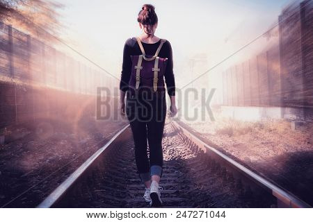 Conceptual image of woman walking into the light. Conceptual photo. Into the light concept. Woman walks into the light on railway tracks. Conceptual. Concept of life.