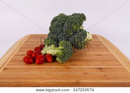 Broccoli Cut Florets And Red Sweet Cherry Tomotoes On A Bamboo Cuttingbaord On Solid Background