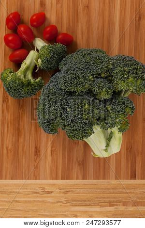 Close Up Green Organic Brocolli Florets And Red Sweet Cherry Tomotes On A Light Wood Background Vert