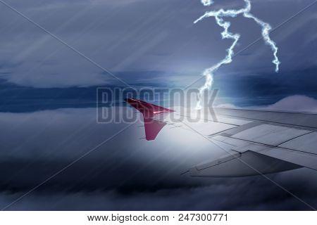 Lightening Strikes Aircraft Wing Of Airplane On Dark Sky