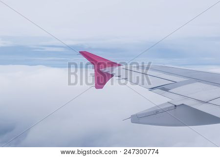Aircraft Wing Of Airplane Flying On Cloud And Bluesky Background