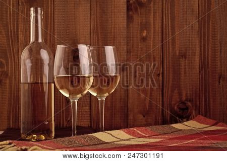 Wine Tasting. One Glass Bottle And Two Bocals Full Of White Wine Standing Close To Each Other On Che