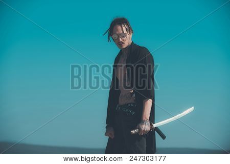 Concentration and zen. Warrior with dreadlocks and open clothes showing tattooed torso. Martial arts concept. Man with katana sword standing on blue sky. Samurai and japan weapon, copy space poster