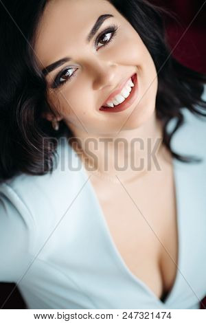 Close up of gorgeous woman with sunny smile looking, posing at camera. Sexy brunette lady with a perfect makeup after beauty salon and in white low neckline dress. Concept of style, fashion. poster