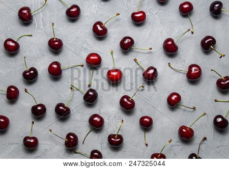 Flat Background: Fresh Ripe Red Cherry Is Evenly Spread Out On A Gray Background. Flatlay.