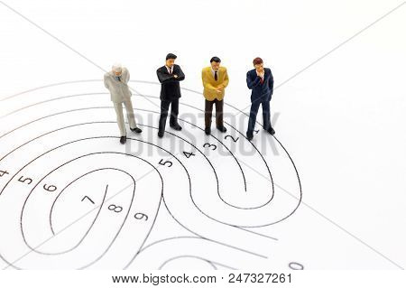 Miniature People: Businessman Standing On Maze And  Thinking How To Solve This Problem. Concepts Of