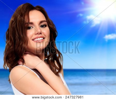 Beautiful woman smiling to you and posing on a beach. Summer holidays concept