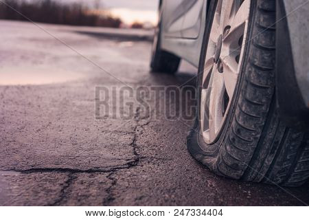 Flat Tyre On Road. Car Tire Leak Because Of Nail Pounding. Toned