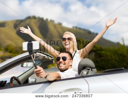 road trip, technology and travel concept - happy couple driving in convertible car and taking picture by smartphone on selfie stick
