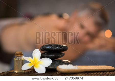 Closeup of stacked black hot stones on wooden table with oil, rock salt and frangipani flower. Zen stones in spa center with cosmetics and massage products. Wellness, beauty and wellbeing concept.