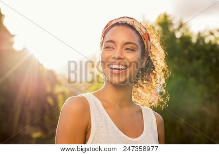poster of Portrait of beautiful african american woman smiling and looking away at park during sunset. Outdoor portrait of a smiling black girl. Happy cheerful girl laughing at park with colored hair band.