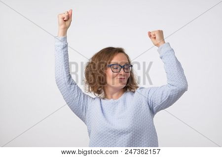 European Girl In Blue Shirt Dancing In Front Of A Gray Wall. She Is Happy And Can Not Stand Calm.