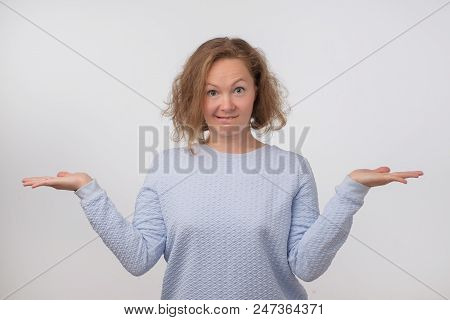 Shrugging Norwegian Woman Wearing Blue Sweater In Doubt Doing Shrug. Confused Girl Gesturing Do Not