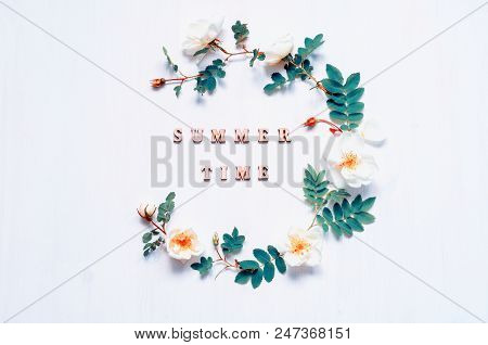 Summer flower background with composition made of white summer rose flowers and Summer time letters. Flat lay, top view. Summer background in vintage tones