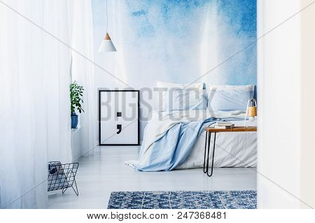 Patterned Rug And Poster In Blue Bedroom Interior With Bed Against Ombre Wallpaper