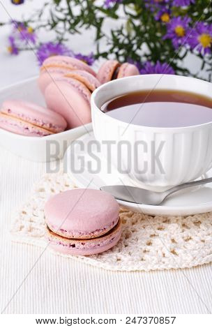 Cup of tea and pink macaroons - French cookies on white table. Teatime. poster