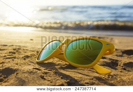 Reflecting Sunglasses In The Sand At The Beach In Summer, The Ocean And The Blue Sky Are Reflecting