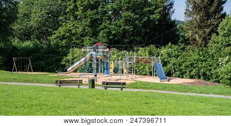Children's Playground With Slide, Climbing Frame And Swing In Nature