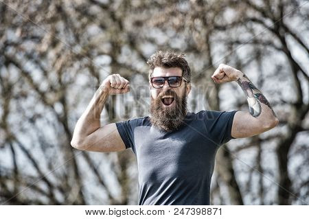 Bearded man shows muscles, biceps on sunny day. Masculinity concept. Man with long beard looks energetic and cheerful. Man with beard and mustache on happy face, branches on background, defocused. poster