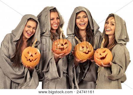 Four smiling nuns in cassocks holding halloween pumpkins