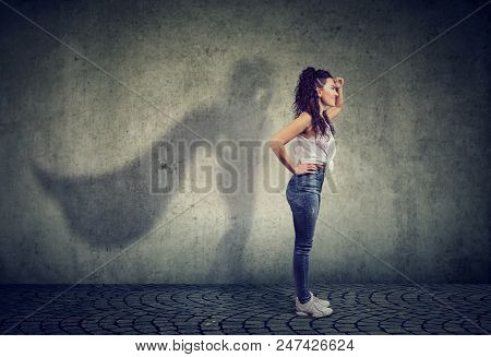 Side View Of A Woman Imagining To Be A Super Hero Looking Aspired.
