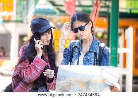 Portrait Of Traveler Woman Find The Way With Friend Together In City. Asian Women Using Map To Find