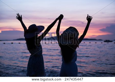 Portrait Of Happy Young Asian Woman Holding Hand Of Her Friend At The Beach. People Enjoying A Toget