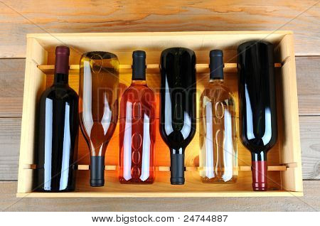A wooden case of assorted wine bottles without labels on a wood plank winery floor. Horizontal format overhead view.