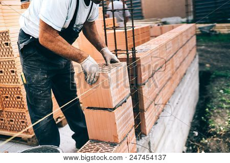 Industrial Worker, Bricklayer, Mason Working With Bricks And Building House