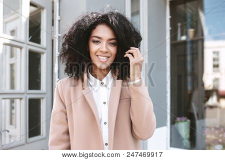 Young Afro-american Girl With Dark Curly Hair Standing In Beige Coat And White Shirt Beautiful Smili