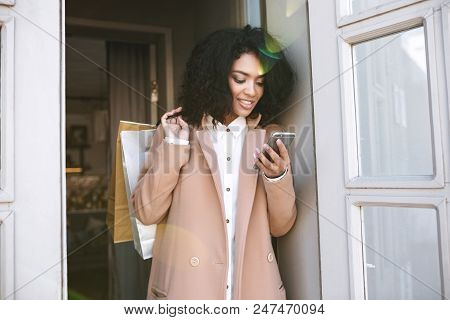 Young African American Girl With Dark Curly Hair Standing With Packets And Phone In Her Hands.pretty