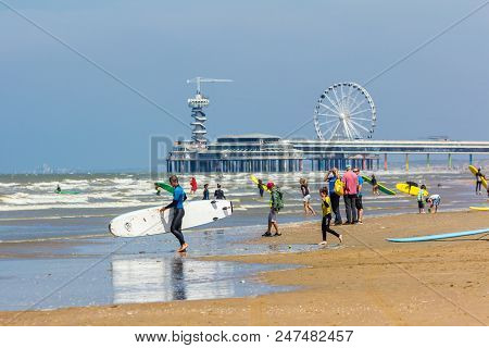 Cheveningen, The Netherlands - June 27 2018: Group Of Young People With Surf Boards On Scheveningen