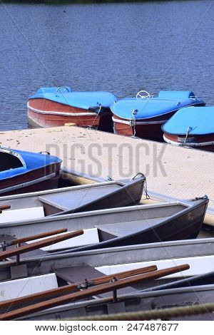 Rural Lake Scene In Bavaria With Row Boat And Pedal Boat On The Dock, Old And Nostalgic Pedal Boats