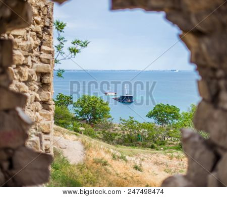 View Of The Sunken Ship Through The Loophole In The Stone Wall Of The Genoese Fortress In Feodosia.