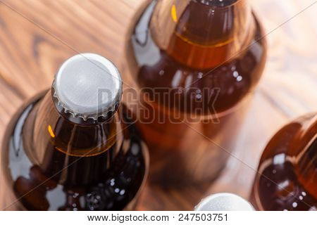 Close Up High Angle View Of Unlabelled Bottles Of Craft Beer With Focus To The Cap On A Single Bottl