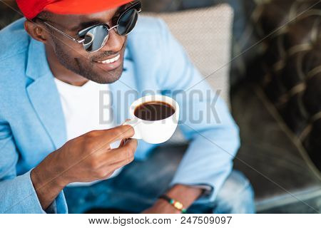 Laughing Man Tasting Mug Of Appetizing Beverage While Relaxing Indoor. Satisfied Employer During Res