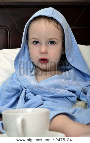 Little Girl In A Blue Robe Resting On The Bed After A Shower With A Cup Of Tea