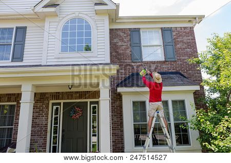 Man Washing The Soffits Or Eaves Of A Modern House Using A Pressure Sprayer On A Hose As He Stands O
