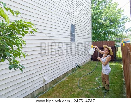 Capable Fit Attractive Woman In A Straw Hat Standing On The Lawn Spraying Down The House Sidings Wit