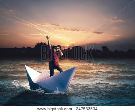 Young Man Navigate On Paper Boat Looking Through Binoculars And Discovers An Tropical Island.