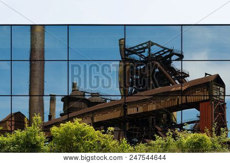Reflection Of Abandoned Industrial Buildings In A Glass Facade Of A Modern Urban Building