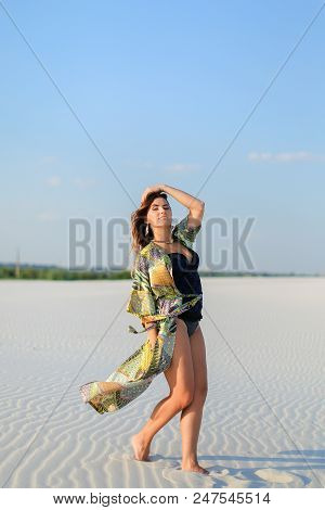 Young Caucasian Woman Wearing Green Beach Robe And Black Swimsuit Standing On White Sand In Windy We