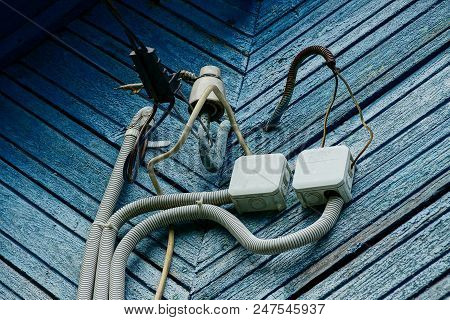 Electrical Cable Wires And Boxes On A Blue Wooden Wall