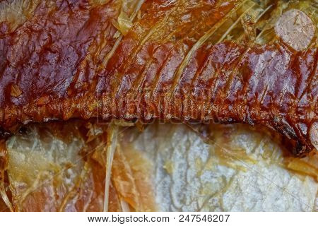 A Piece Of Brown Smoked Fish With Bones